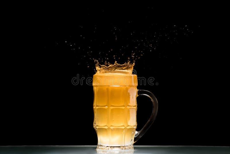 glas licht bier met plonsen bij lijst aangaande zwarte achtergrond royalty-vrije stock foto