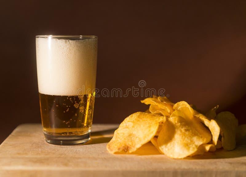 Glas licht bier met schuim, spaanders op een houten Raad op een donkere achtergrond, alcoholische drank, snack stock fotografie