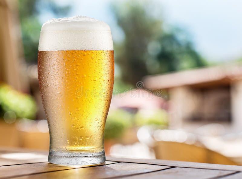 Glas licht bier op een houten lijst stock foto