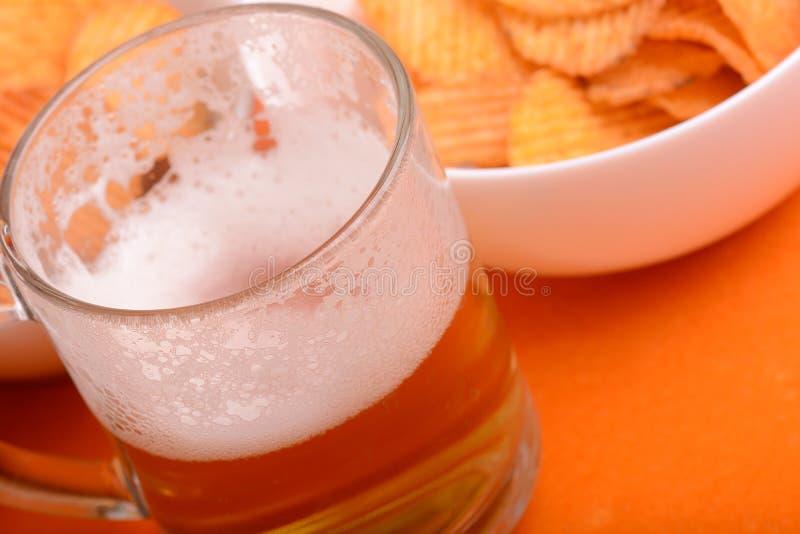 Glas lichte bier en chips op een houten lijst stock foto
