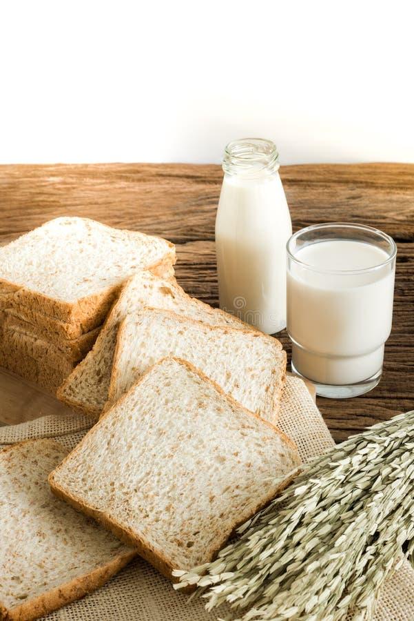 Glas melk en geheel tarwebrood op de houten raad royalty-vrije stock afbeeldingen