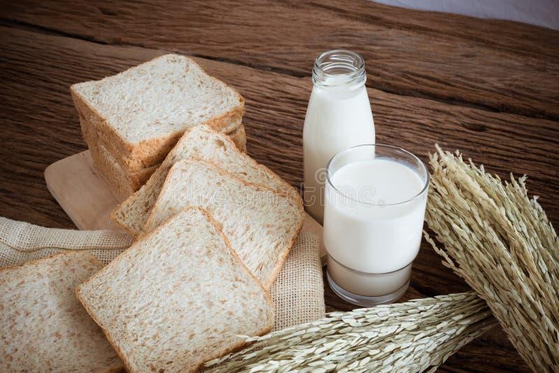 Glas melk en geheel tarwebrood op de houten raad stock fotografie