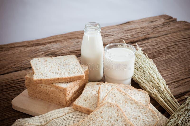 Glas melk en geheel tarwebrood op de houten raad stock foto