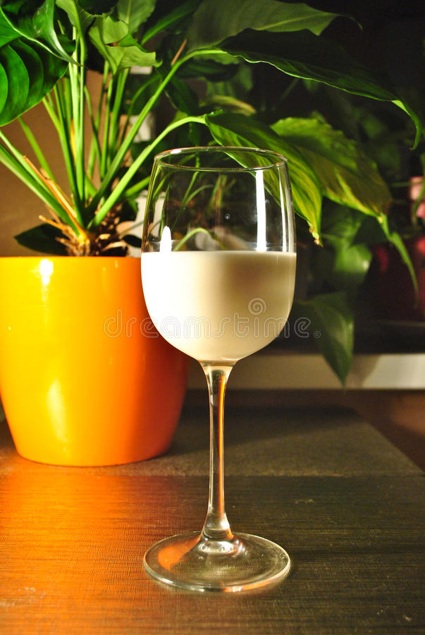 Glas melk op de lijst Vullend proces stock foto