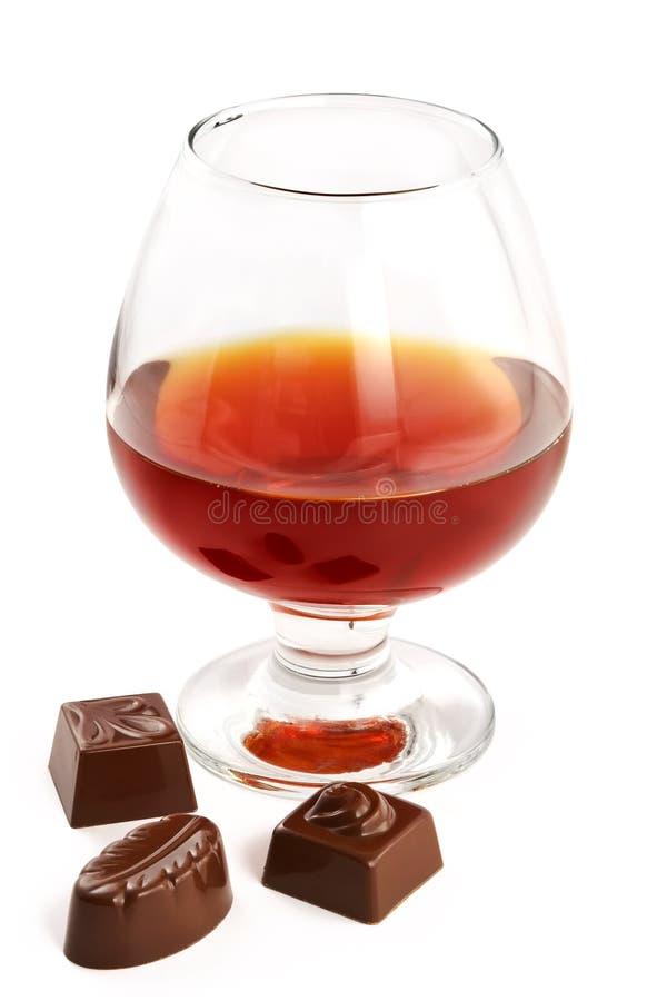 Glas met cognac en snoepjes met alcoholische drank stock fotografie