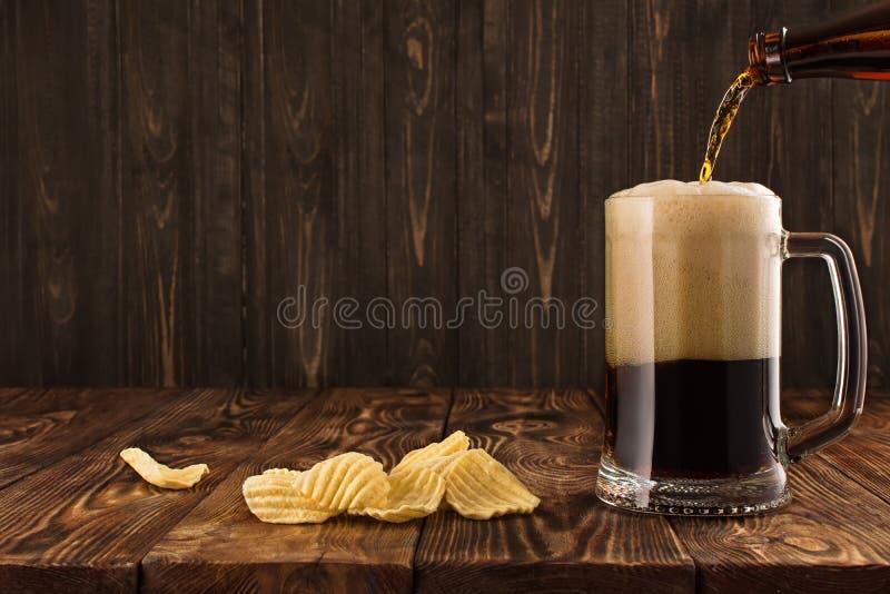 Glas met een donker bier op een houten lijst stock afbeeldingen
