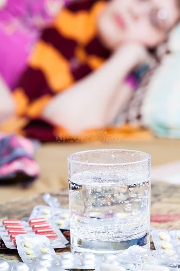 Glas met geneesmiddel en stapel van pillen op lijst royalty-vrije stock afbeelding