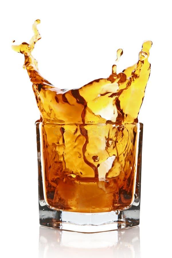 Glas met het bespatten van wiskydrank stock afbeelding