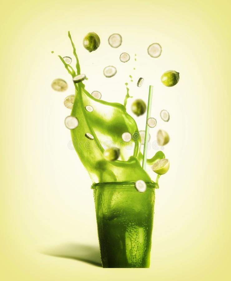 Glas met het drinken stro en de groene drank van de plonszomer: smoothie, sap of limonade met vliegende ingrediënten royalty-vrije stock foto