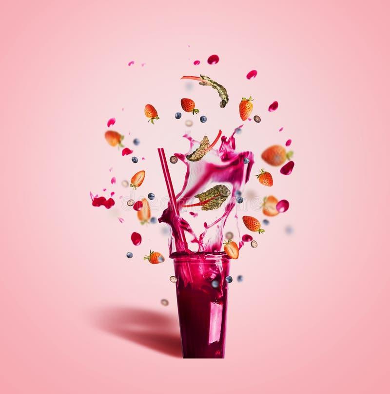 Glas met het drinken stro en de purpere drank van de plonszomer: smoothie of sap met vliegende besseningrediënten op roze royalty-vrije stock foto's