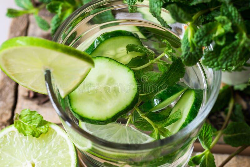 Glas met het verfrissen van detox komkommerwater met verse munt en kalk op de de schuur houten doos, ingrediënten, lente of zomer stock foto's