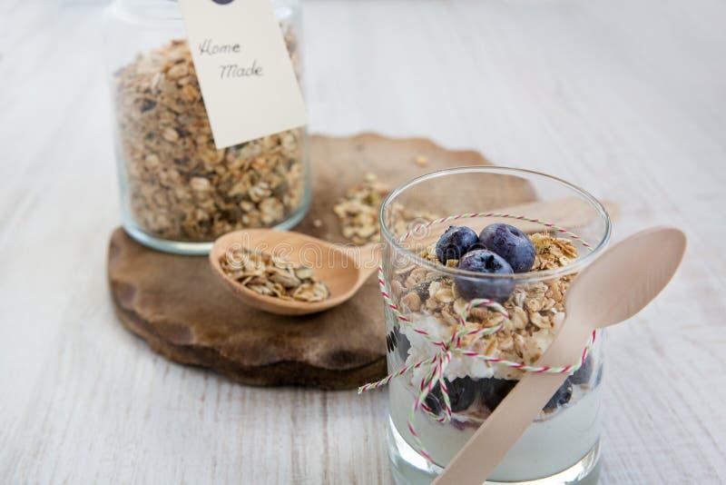 Glas met natuurlijke yoghurt en kruik met naar huis gemaakte muesli stock foto's