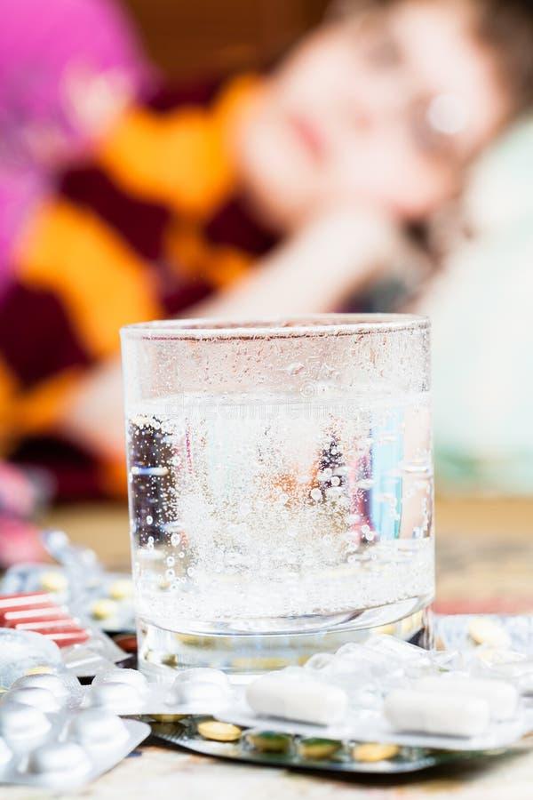 Glas met opgelost geneesmiddel in water en pillen royalty-vrije stock fotografie