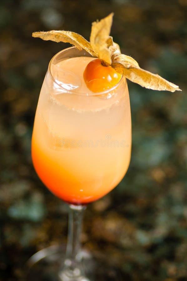 Glas met oranje cocktail wordt gevuld die stock afbeelding
