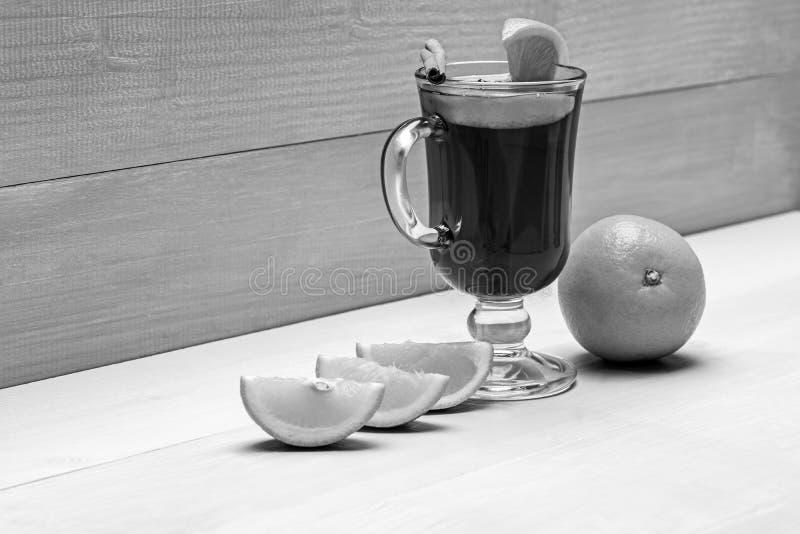 Glas met overwogen wijn of hete cider dichtbij sappig oranje fruit op witte houten achtergrond Drank of drank met sinaasappel royalty-vrije stock fotografie