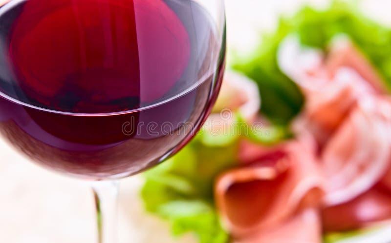 Glas met rode wijn en ham royalty-vrije stock afbeelding
