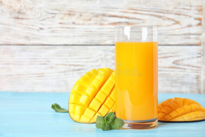 Glas met vers mangosap en smakelijke vruchten op houten lijst stock fotografie
