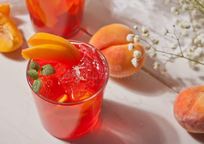 Glas met verse eigengemaakte perzik zoete bevroren thee of cocktail, limonade met munt Verfrissende koude drank De zomerpartij royalty-vrije stock afbeeldingen