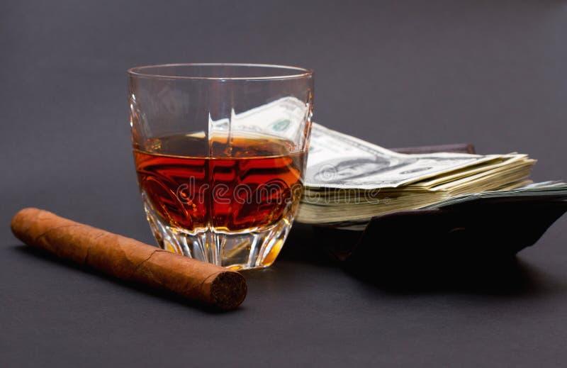 Glas met whisky, sigaar en een partij van geld op een bruine portefeuille op de donkere achtergrond royalty-vrije stock foto's