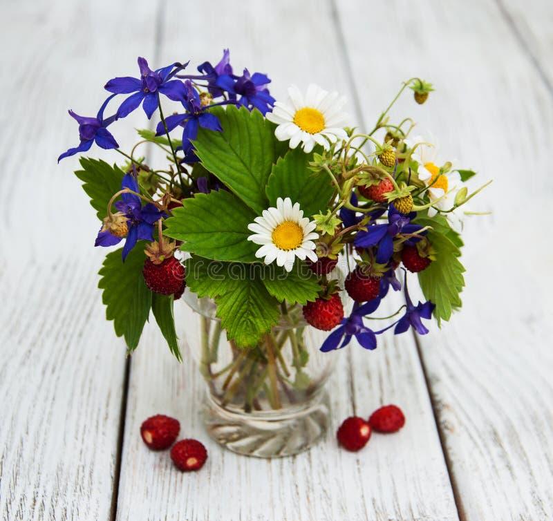 Glas met wilde aardbeien en wildflowers royalty-vrije stock afbeeldingen