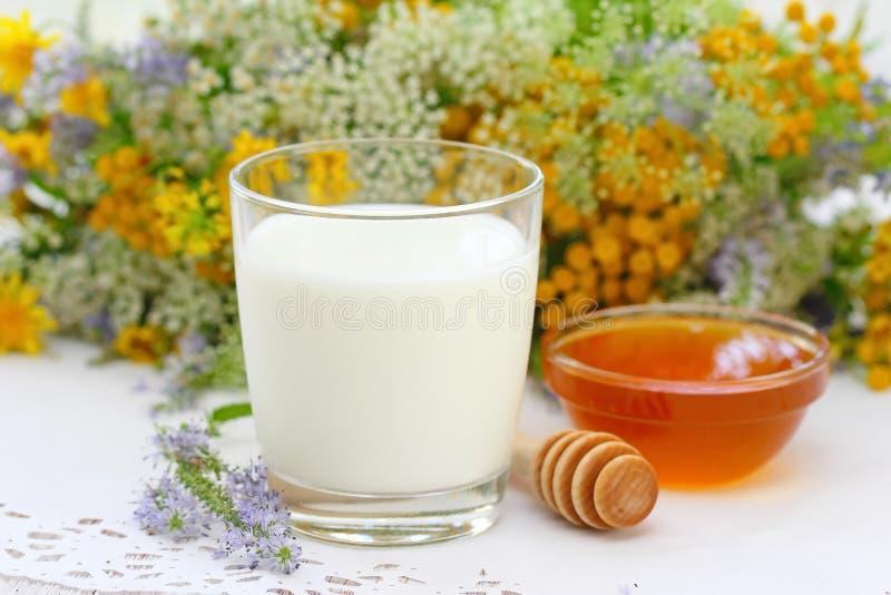 Glas Milch- und Blumenhonig in einer Schüssel lizenzfreie stockfotos
