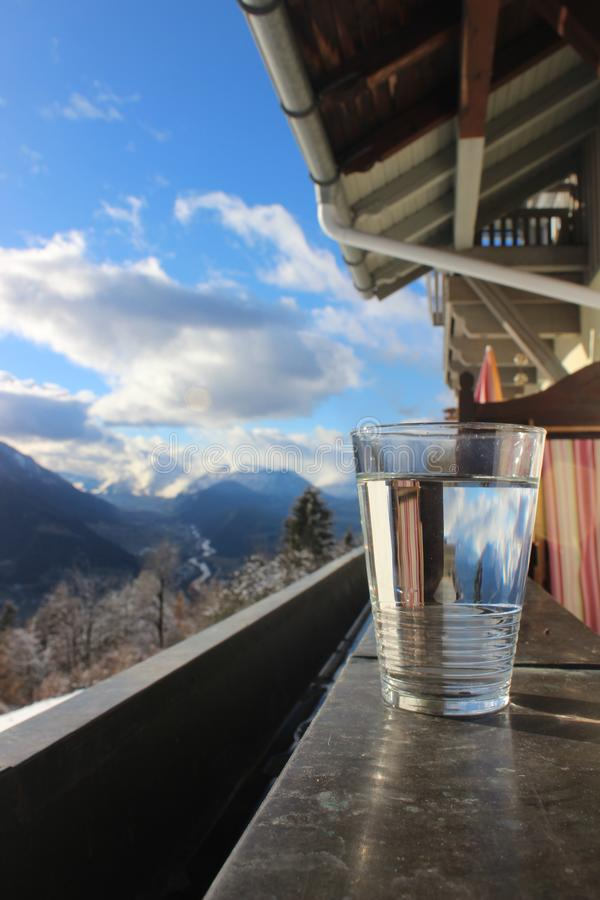 Glas of mineral water with mountain landscape and blue cloudy sky stock images
