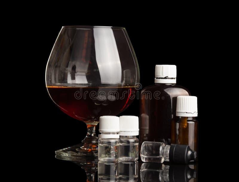 Glas mit Alkohol, Satz Flüssigkeiten für das Rauchen einer elektronischen Zigarette, lokalisiert auf Schwarzem lizenzfreie stockfotografie