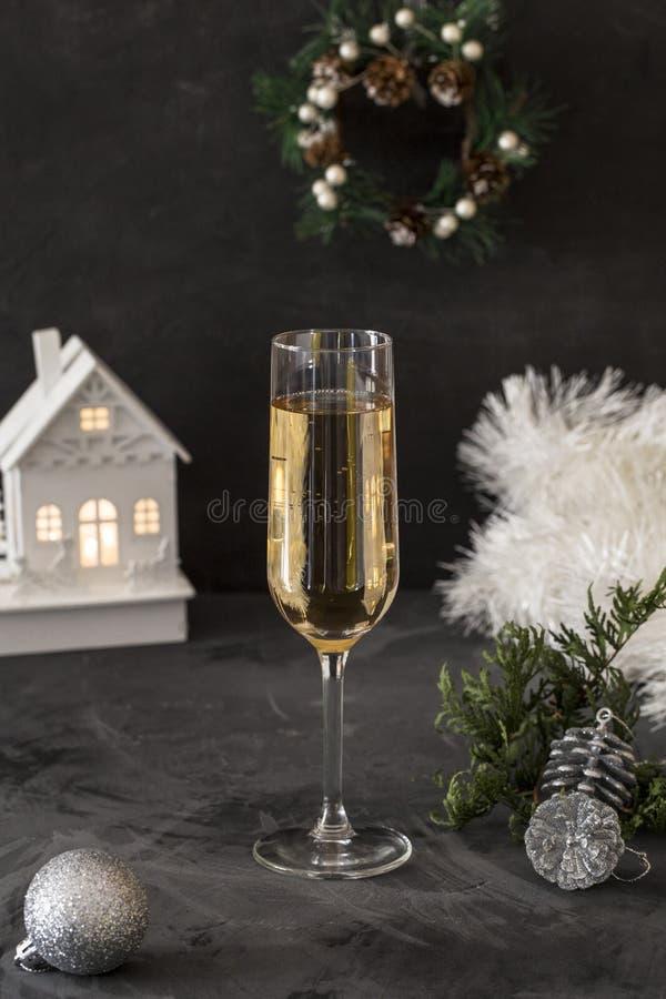 Glas mit Champagner mit Lametta am schwarzen Hintergrund lizenzfreie stockfotografie
