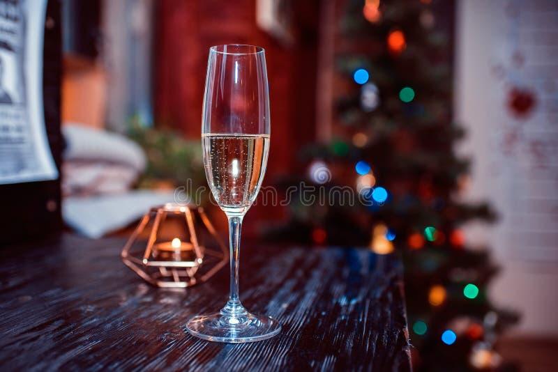 Glas mit Champagner vor dem hintergrund einer Kerze und eines Tannenbaums lizenzfreie stockfotografie