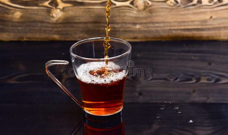 Glas mit dem Tee, der mit Flüssigkeit mit ausläuft, spritzt und Wassertropfen Brauenteekonzept Schale, die mit Wasser oder Tee gi stockbild