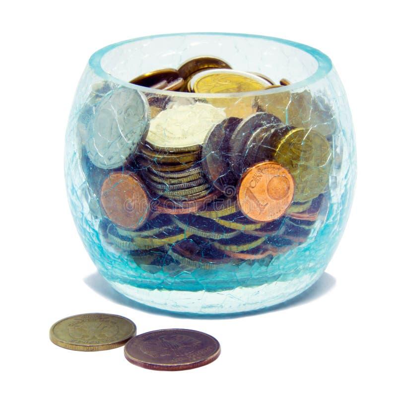 Glas mit den Münzen, lokalisiert auf weißem Hintergrund stockbild