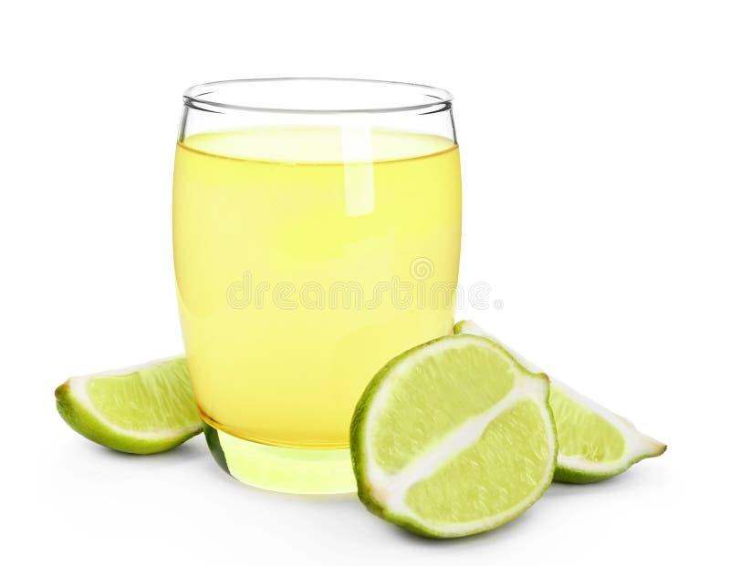 Glas mit frischem Zitrusfruchtsaft und geschnittenem Kalk auf wei?em Hintergrund lizenzfreie stockfotos