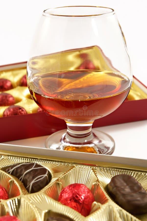Glas mit Kognak und Bonbons mit Alkohol stockfotografie
