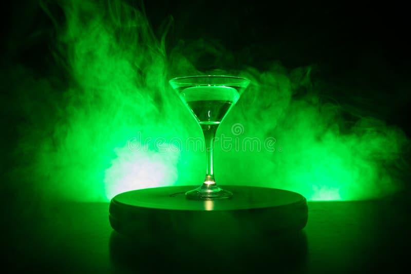 Glas mit Martini mit Olive nach innen Schließen Sie herauf Ansicht des Glases mit Vereingetränk auf dunklem nebeligem getontem Hi lizenzfreies stockbild