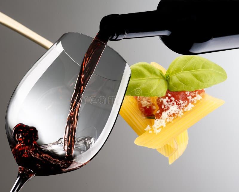 Glas mit Rotwein und Gabel mit Makkaroni lizenzfreies stockbild
