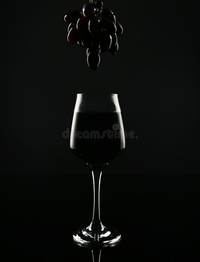 Glas mit Rotwein und geschmackvollen frischen Trauben auf schwarzem Hintergrund lizenzfreie stockfotografie