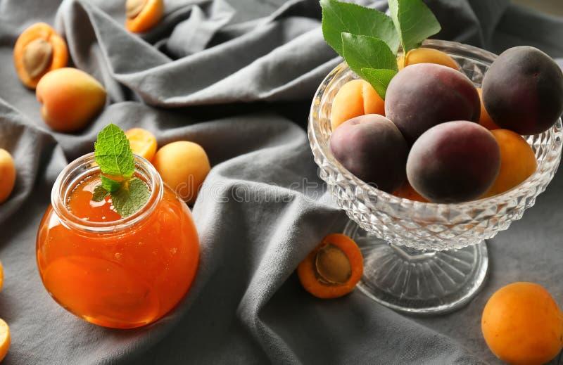 Glas mit süßer Aprikosenmarmelade und frischen Früchten auf Tabelle stockbilder
