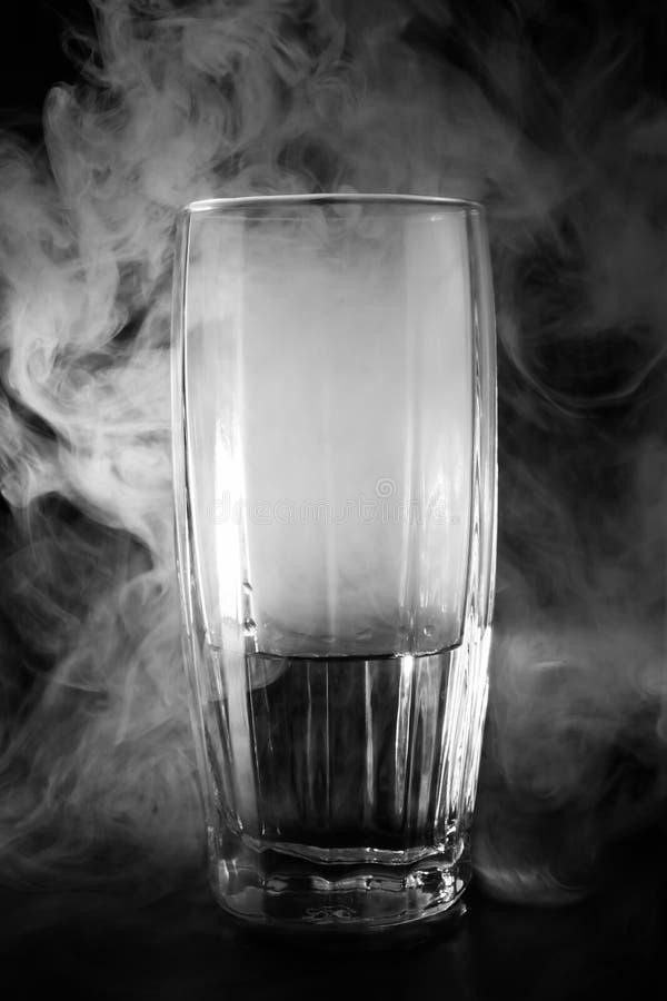 Glas mit Wasser und Rauche auf einem dunklen Hintergrund, abstrakt Hintergrund lizenzfreies stockfoto