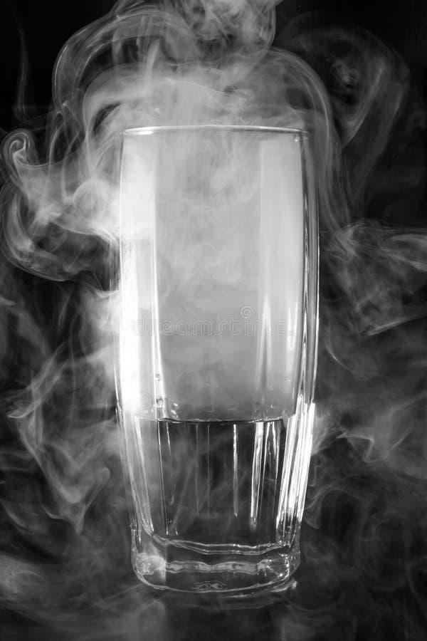 Glas mit Wasser und Rauche auf einem dunklen Hintergrund, abstrakt Hintergrund lizenzfreie stockfotografie