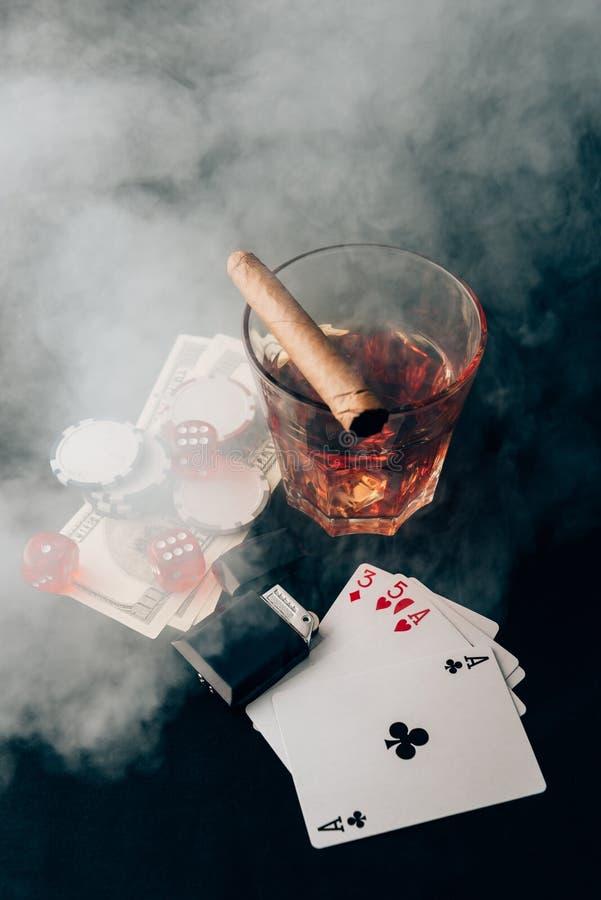 Glas mit Whisky und Zigarre auf Tabelle mit Karten stockfotografie