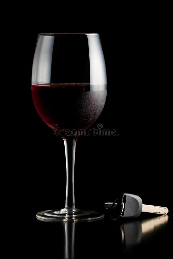 Glas rode wijn en autosleutels stock fotografie