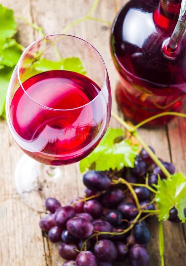 Glas rode wijn met druif op rustieke houten achtergrond royalty-vrije stock afbeelding