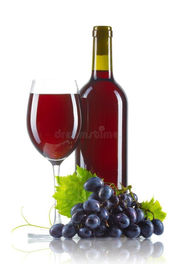 Glas rode wijn met geïsoleerde fles en rijpe druiven royalty-vrije stock fotografie