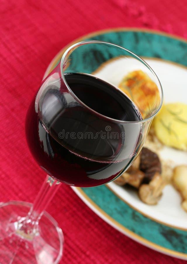 Glas rode wijn met maaltijd royalty-vrije stock afbeelding