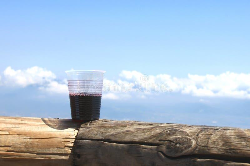 Glas rode wijn op achtergrond van wolken en blauwe hemel royalty-vrije stock afbeelding