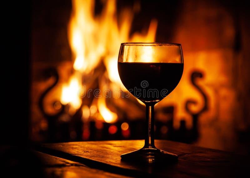 Glas rode wijn op de houten lijst met het branden van brand op de achtergrond Het gelijk maken ontspant op comfortabele plaats Do stock fotografie