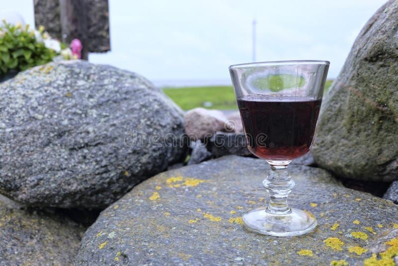 Glas rode wijn op de rotsen stock foto