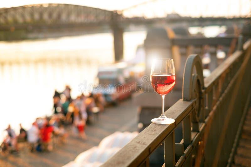Glas rode wijn op een traliewerk met zonsondergang in een stad van Praag Concept vrije tijd in de de stad en het drinken alcohol royalty-vrije stock foto