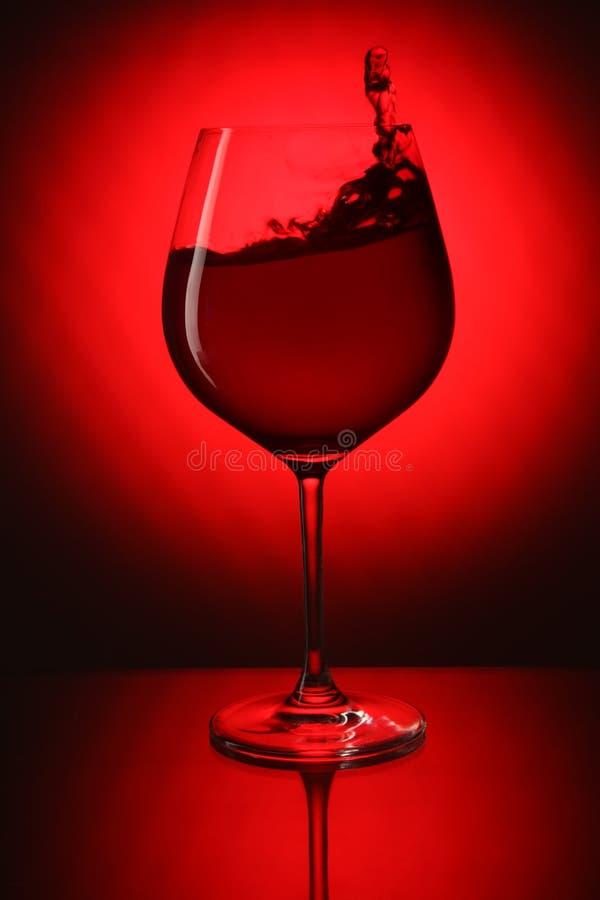 Glas rode wijn op rode achtergrond royalty-vrije stock foto
