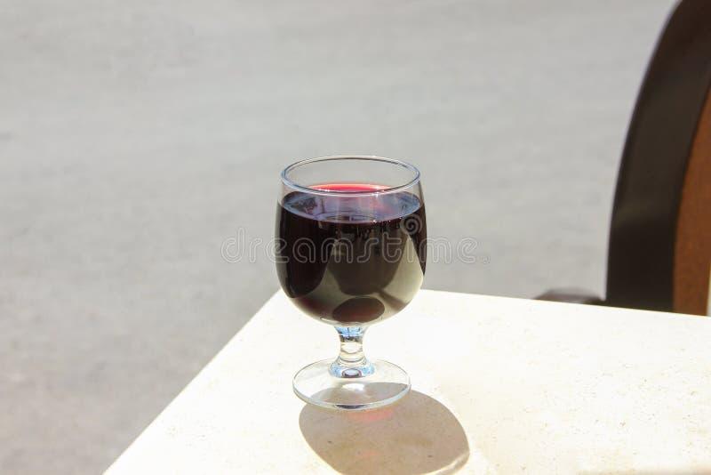 Glas rode wijn op witte lijst in de zomerkoffie in zonnige dag stock foto's